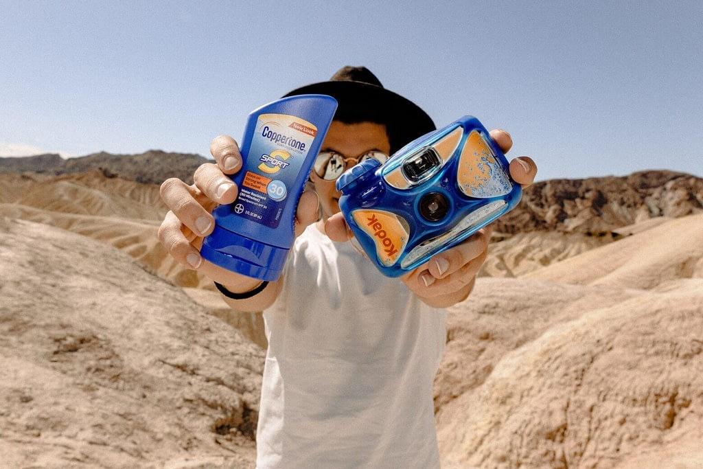 Man Holding Sunscreen Lotion Bottles